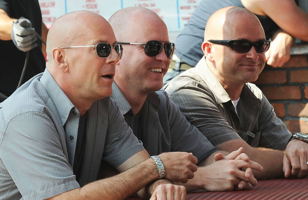 """Bruce Willis (L) and his """"doubles"""" on location ©Bobby Bank/WireImage/Getty Images"""